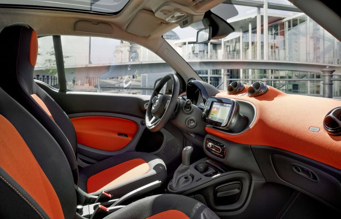 Der neue smart fortwo, 2014 Polsterung in Stoff schwarz/orange, Instrumententafel und Türmittelfelder in Stoff orange und Akzentteile in schwarz/grau, smart Media-System The new smart fortwo, 2014 Upholstery in black / orange fabric, Dashboard and door centre panels in orange fabric and contrast components in black/grey, smart media system